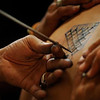 A Thai Buddhist artist draws a traditional tattoo on the back of a devotee.