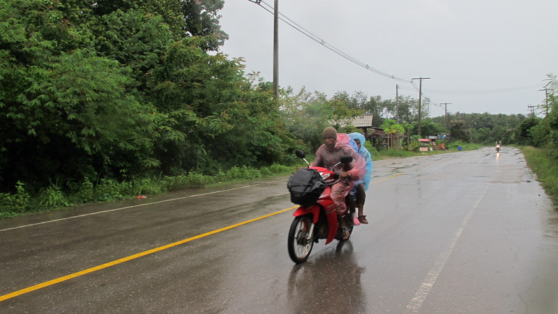 A family is well wrapped up in rain gear while riding a motorbike in the rain on Koh Lanta