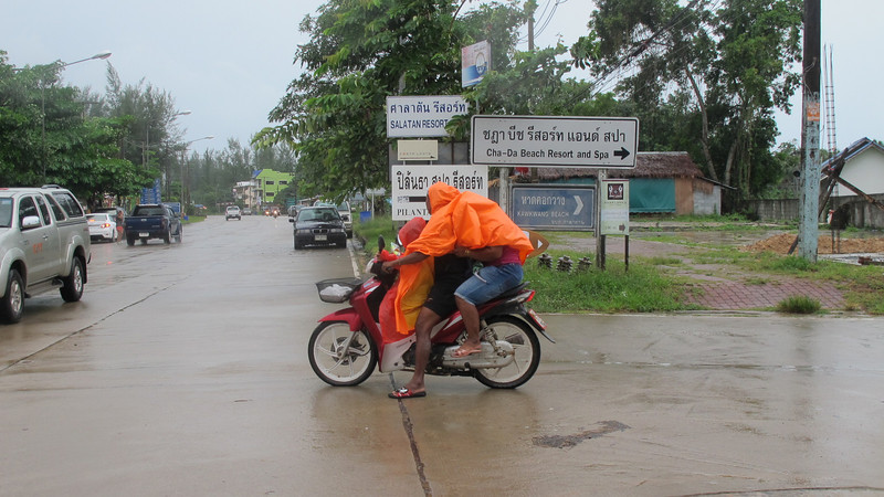 An entire family on a motorbike tries to stay dry in the rain in Koh Lanta