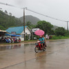 A family shelters under an umbrella while riding a motorbike on Koh Lanta