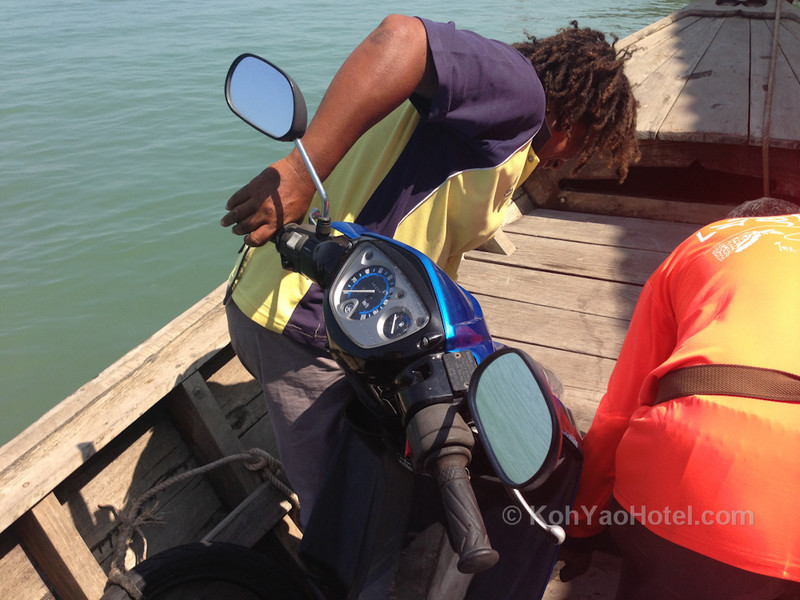 carrying the motorbike on to the longtail boat to travel from koh yao noi to koh yao yai