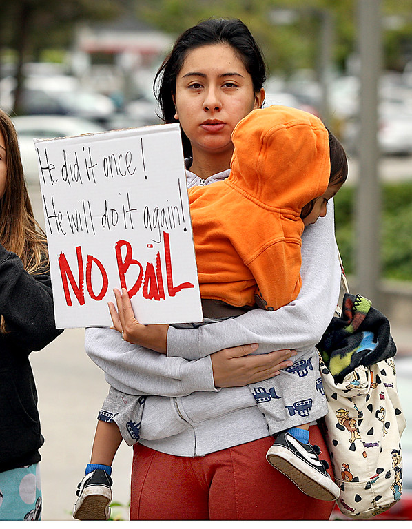 . A woman holding her daughter protests outside the courthouse where accused child molesting neurosurgeon James Kohut\'s bail was set at $6.4 million Wednesday.  (Dan Coyro -- Santa Cruz Sentinel)
