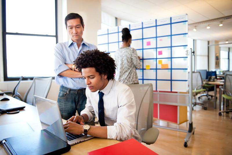 Boss Looking Over Employee's Shoulder in Office