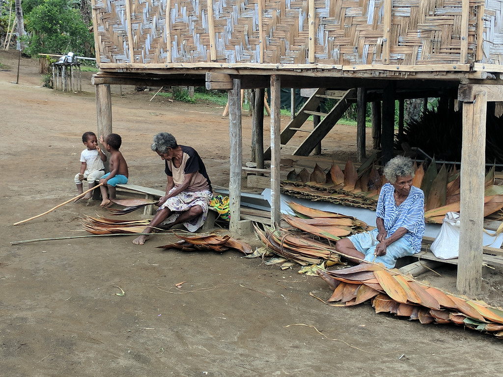Ladies tying together leaves for roofing