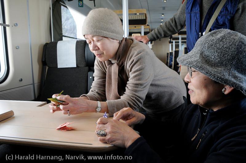 31.3.2011: Japanske turister på Nordkalott-tur, her demonstrerer fenomenale ferdigheter med origami (papirbrettekunst) for medpassasjerer på Ofotbanen på tur til Narvik.