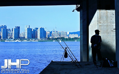 A fisherman waits patiently along the South side of the Han River, looking north toward the tower, beneath a highway underpass. Print KOR3B-919-132