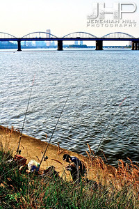 A fisherman with several rods, along the South side of the Han River, looking West, toward the 63 Building. Print KOR3B-919-080