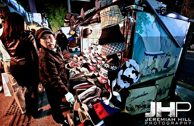 A street seller hawking hats in mid October. Itaweon district, Seoul. Print KOR3B-1018-070
