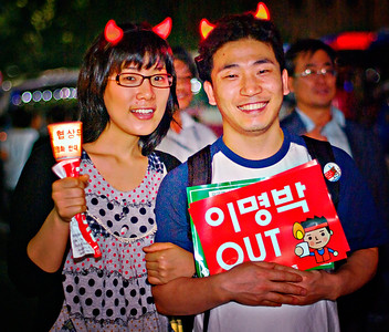 "Typical young couple with a ""Lee Myung-bak OUT"" sign."