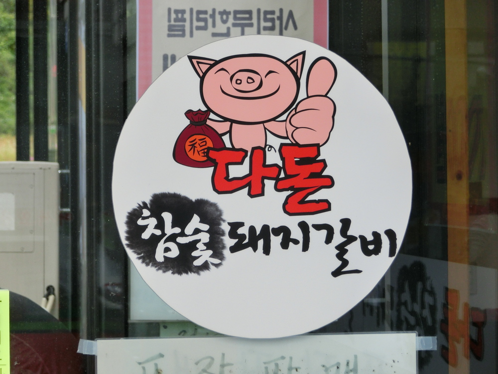 Korean pig inviting you in to the restaurant to eat