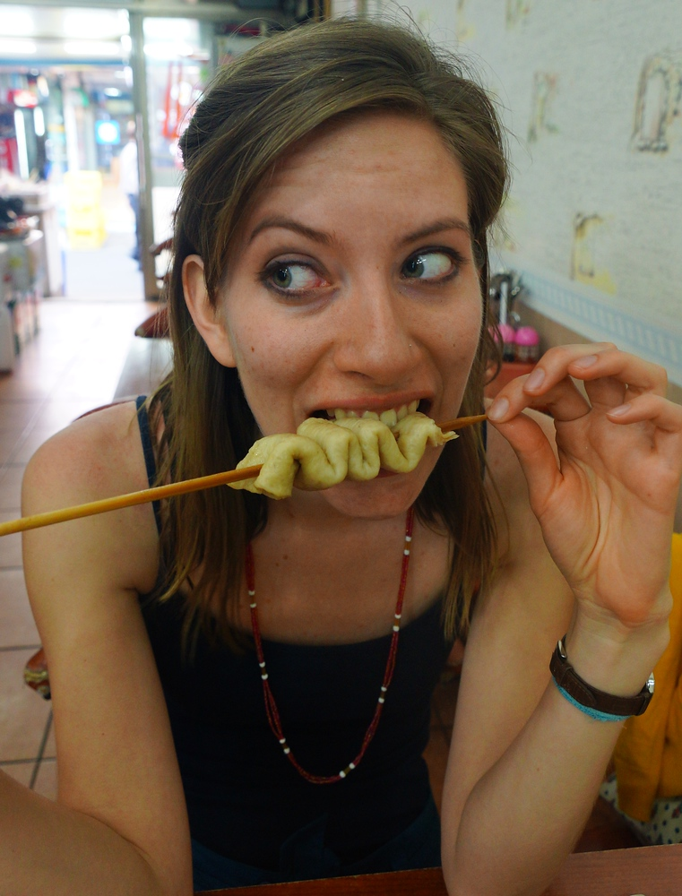 Audrey Bergner (That Backpacker) eating Korean fish cakes on a skewer