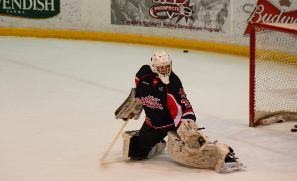 UNB Hockey goalie making a save during a warm-up drill in Fredericton
