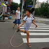 "A girl skips across the side-walk with a jump-rope - Incheon, South Korea.  This is a travel photo from Incheon, South Korea. <a href=""http://nomadicsamuel.com"">http://nomadicsamuel.com</a>"