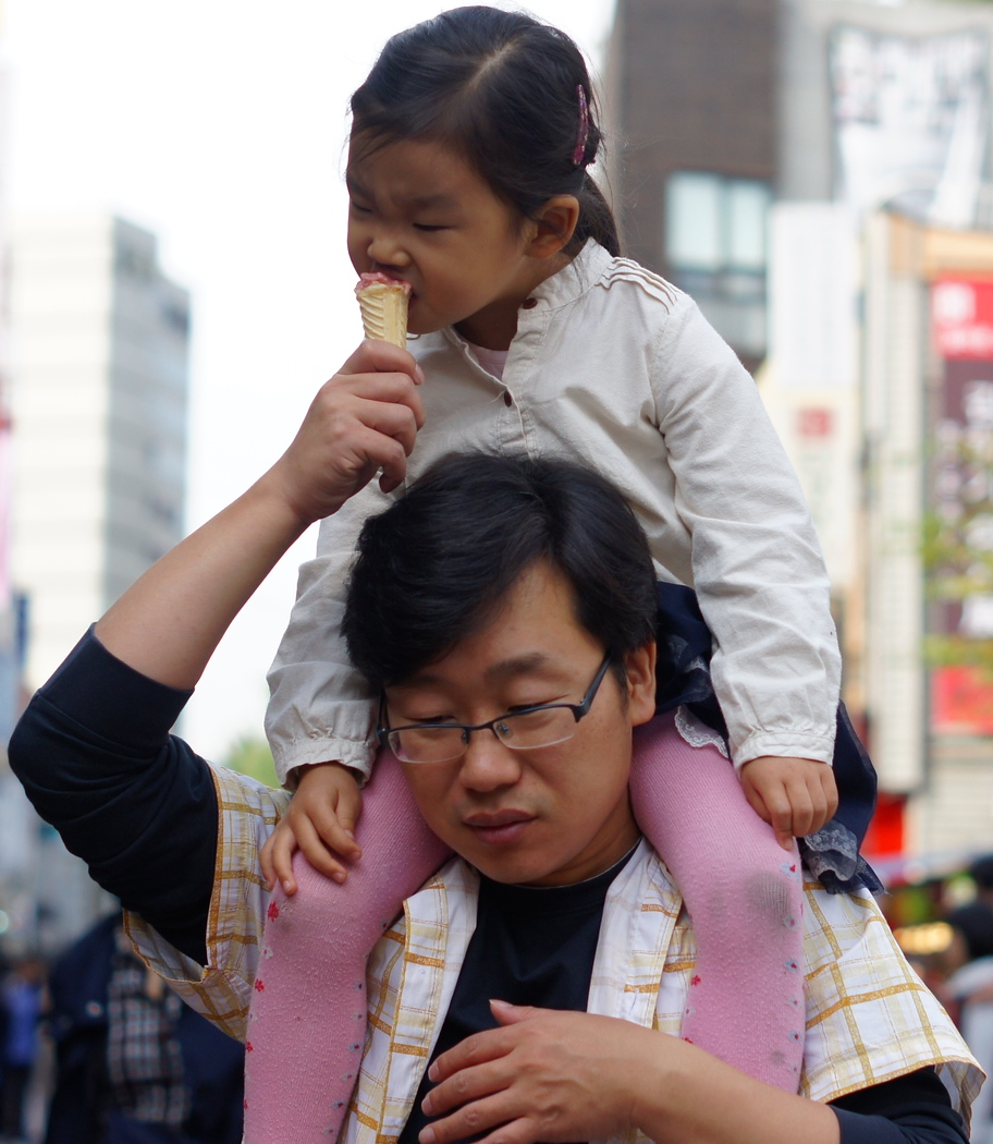 A small girl taking a bite of an ice cream cone while being carried by her father - Insadong : Seoul, Korea.  To view my gallery from Insadong - Seoul, Korea click on the photo.