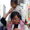 "A small girl taking a bite of an ice cream cone while being carried by her father - Insadong : Seoul, Korea.  To view my gallery from Insadong - Seoul, Korea click on the photo. <a href=""http://nomadicsamuel.com"">http://nomadicsamuel.com</a>"