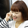 Today's daily travel photo is of a Korean lady smiling while talking on the phone while riding the Seoul subway from Incheon into the city in South Korea.