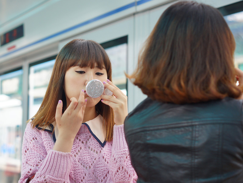 Today's daily travel photo is a shot of a Korean woman putting on the final touches of her make-up at a metro station in Seoul, South Korea.
