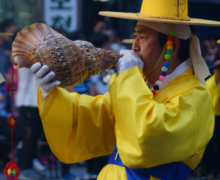 Today's daily travel photo is of a Korean male performer wearing an entirely yellow traditional outfit playing music during the Lotus Lantern Festival in Seoul, South Korea.