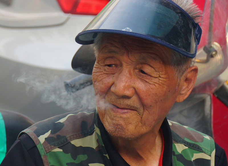 Today's daily travel photo is of a Korean man wearing military inspired attire puffing out smoke from his mouth as he sits on a curb in Seoul, South Korea.