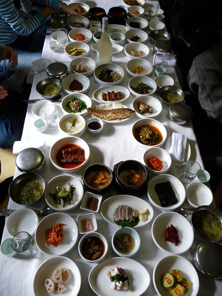 An overhead photo of a Korean feast in Gyeongju, South Korea.  The following Korean cuisine includes mains, side dishes & soups along with rice.