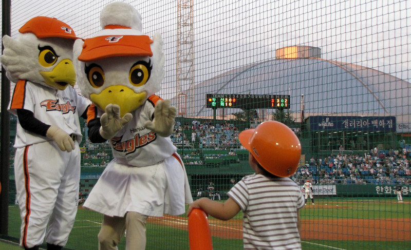 Today's daily travel photo is of a cute Korean boy interacting with the Hanhwa Eagles mascots at a Korean professional baseball game in Daejeon, Korea.