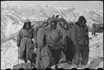 These frostbite casualties of the embattled First Marine Division and Seventh Infantry Division who linked up in the Chosin Reservoir area in a desperate attempt to break out of Communist encirclement wait with set expressions on their faces for pickup by planes of the U.S. Air Force Far East Combat Cargo Command.