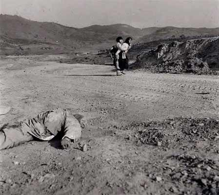 A Korean woman carries a child past a dead ROK soldier.