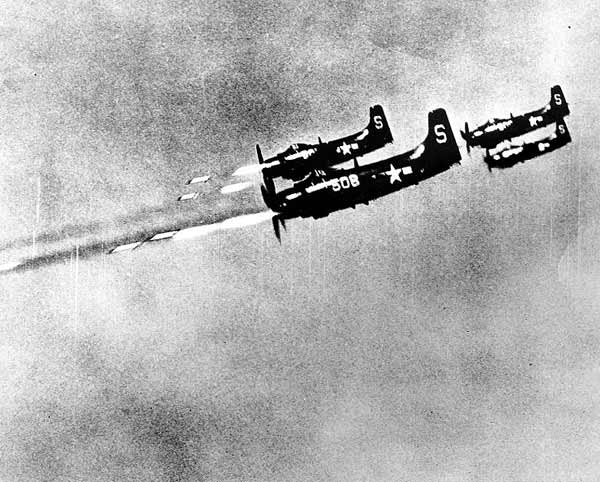 """USS Valley Forge """"Skyraider"""" attack planes fire 5-inch rockets at a North Korean field position. Photo is dated 24 October 1950."""