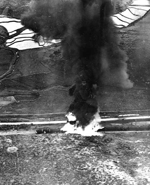 A fuel or ammunition train burns near Kumchon, North Korea, after being hit by planes from USS Valley Forge (CV-45). Photographed on the morning of 22 July 1950.