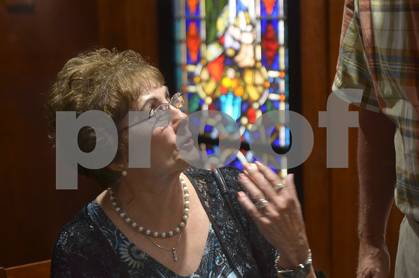 -Messenger photo by Jesse Major<br /> Mary Jo Schlapia sits in the new chapel at Kossuth Regional Health Center during its dedication Sunday. The stained-glass window behind her is the same that was in the hospital's previous chapel, before it was removed in the 1970s.
