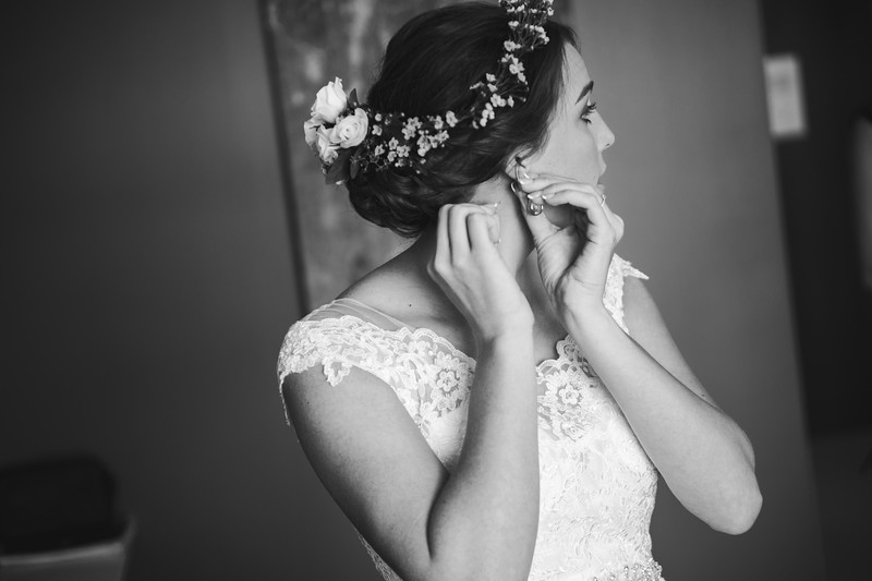 Bride putting earings on.