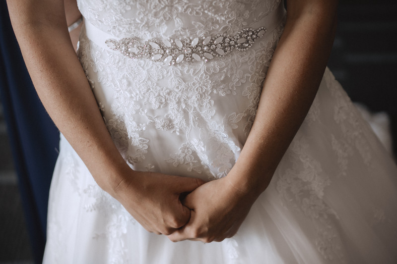 Bride holding her hands in front of her dress.