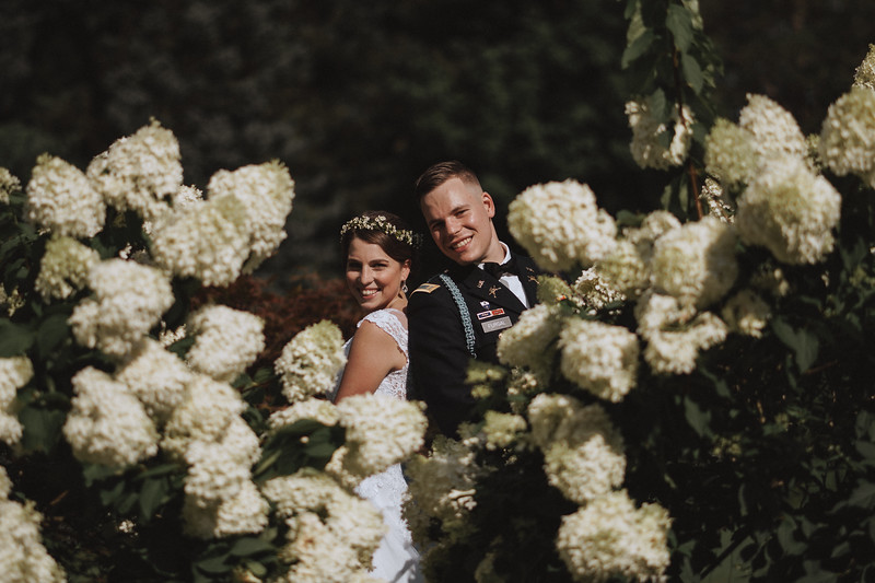 The bride and groom pose back to back and peer out at the camera from behind large white flowers.