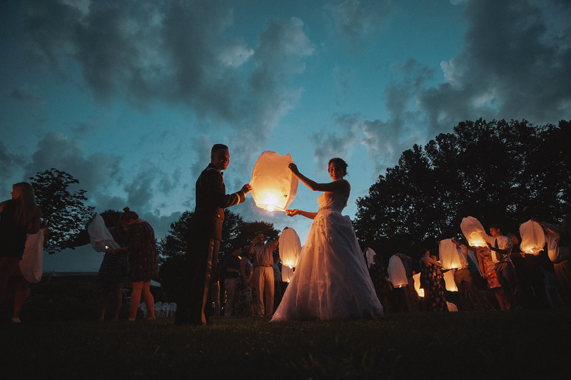 The bride and groom smile as they prepare to release the lantern into the sky.