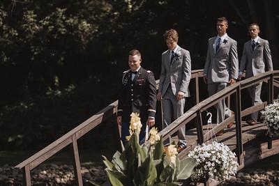 The groom walking over a bridge followed by his groomsmen.