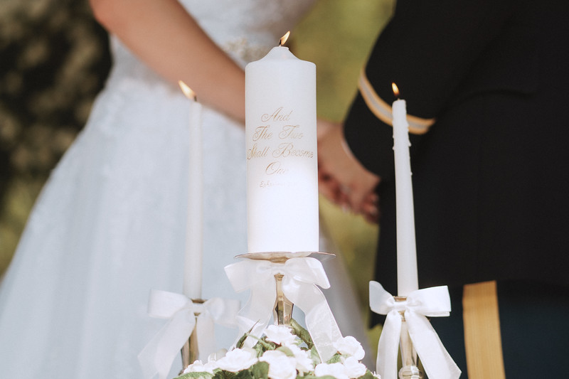 Lit unity candle with bible verse flickers in front of the bride and groom.