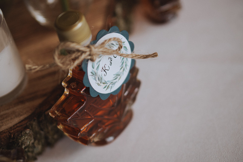 Maple leaf shaped glass bottle of maple syrup with twine holding a tag with a guests name printed on it.