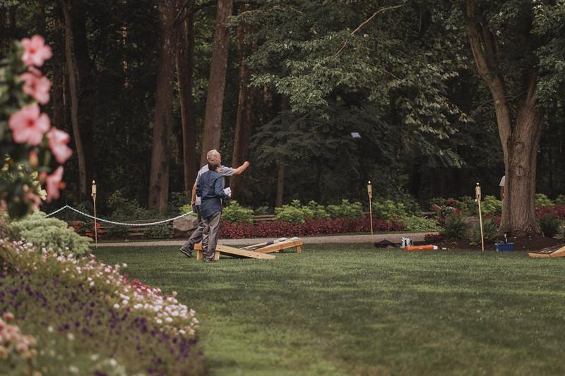 A man and a boy play bean bag toss.