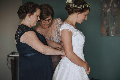 Bride's mother and sister helping to button up her wedding gown.