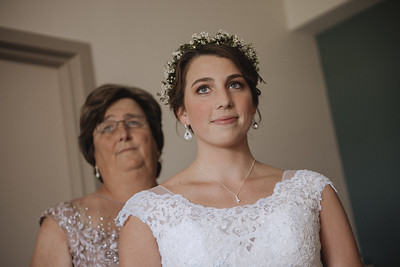 Bride smiling with her mother behind her.