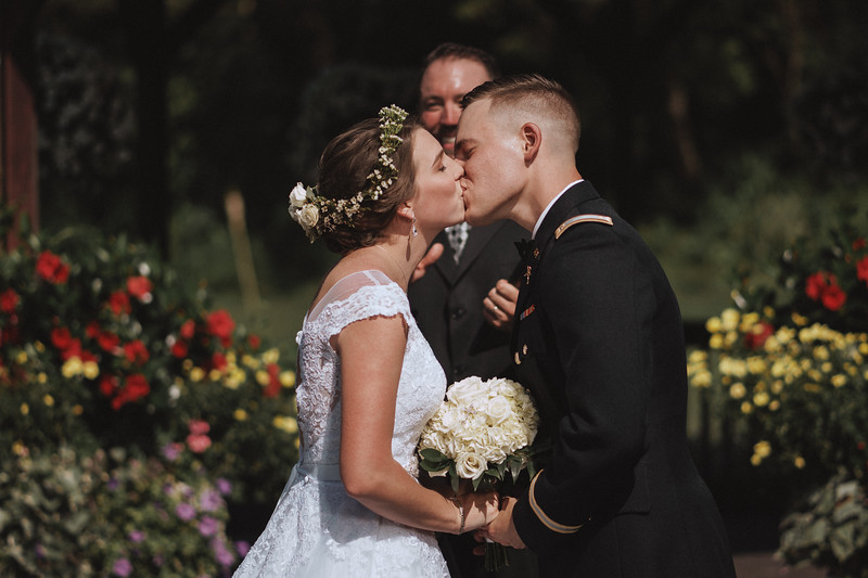 Newly married, the bride and groom kiss for the first time as husband and wife.