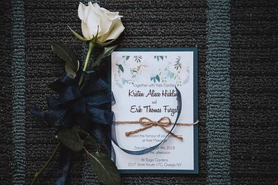 Flower with a ribbon bow around it next to a wedding invitation.