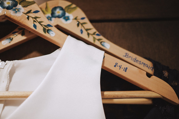 Hand painted flowers on wooden hangers.
