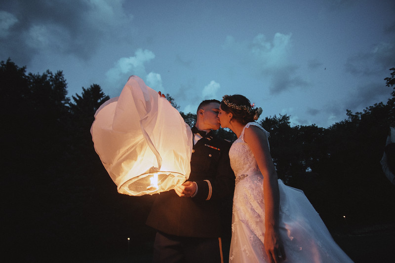 The bride and groom kiss as they light a Chinese lantern.
