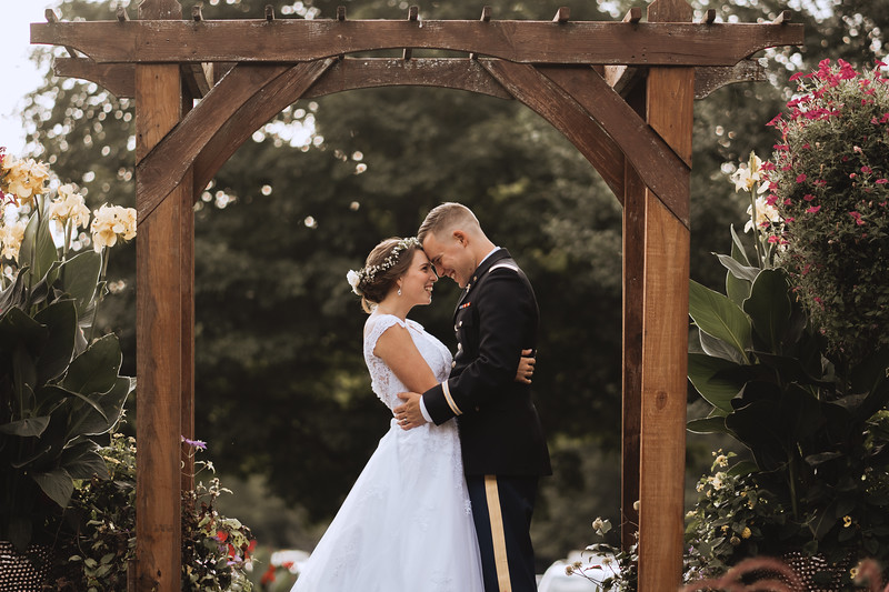 The bride and groom laugh and touch foreheads under an arbor surrounded by flowers and lush plants.
