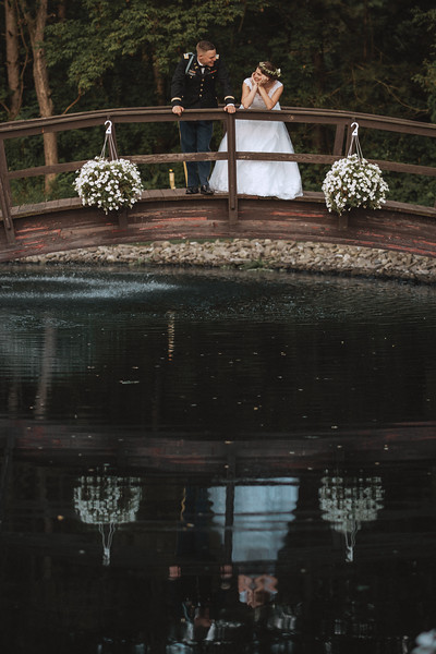 The bride and groom smile at each other on a bridge as they're reflected in the pond.