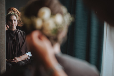 Bride smiling in a mirror as her hair gets done.