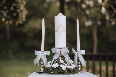 """Ornate candles on a table surrounded by flowers. A large candle has the words """"And the two shall become one. Ephesians 3:3"""" written on it."""