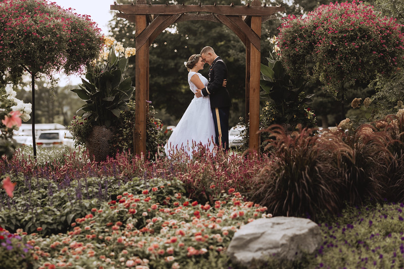 The bride and groom laugh as they touch foreheads under an arbor surrounded by flowers and lush plants.
