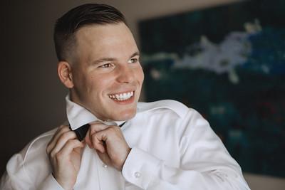 Groom smiling as he ties his bow tie.